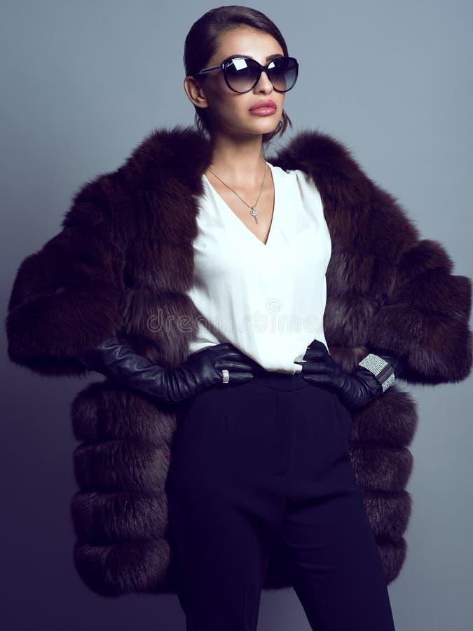 De mooie blouse van de glam model dragende witte zijde, zwarte broek, sabelmarterlaag, leerhandschoenen en suglasses stock afbeeldingen