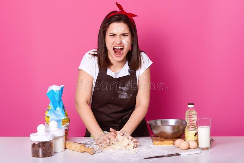 De mooie boze die kok kneedt deeg en gilt luid, zijnd ziek en vermoeit van het voorbereiden van eigengemaakt gebakje Woedende don royalty-vrije stock afbeeldingen