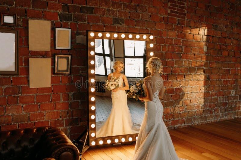 De mooie bruid bevindt zich dichtbij de spiegel en onderzoekt haar gedachtengang royalty-vrije stock afbeeldingen