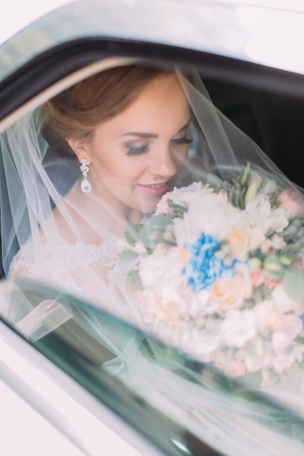 De mooie bruid die het huwelijksboeket ruiken onder de sluier terwijl het zitten in de auto stock afbeeldingen