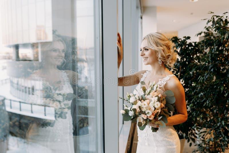 De mooie bruid in een witte kleding bevindt zich dichtbij het venster in hypermarket, blonde stock afbeelding
