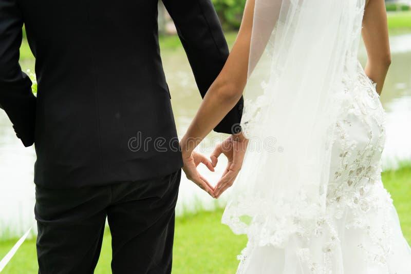 De mooie bruid en bruidegomgreep dient hartvorm, parenhuwelijk voor altijd met liefde in royalty-vrije stock fotografie
