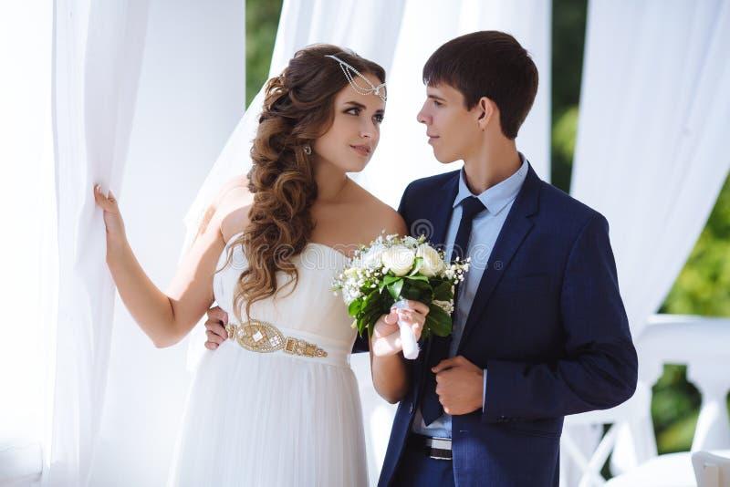 De mooie bruid is gekleed in een Griekse stijlkleding, is haar haar verfraaid met parels, houdt zij een schrijver uit de klassiek stock foto's