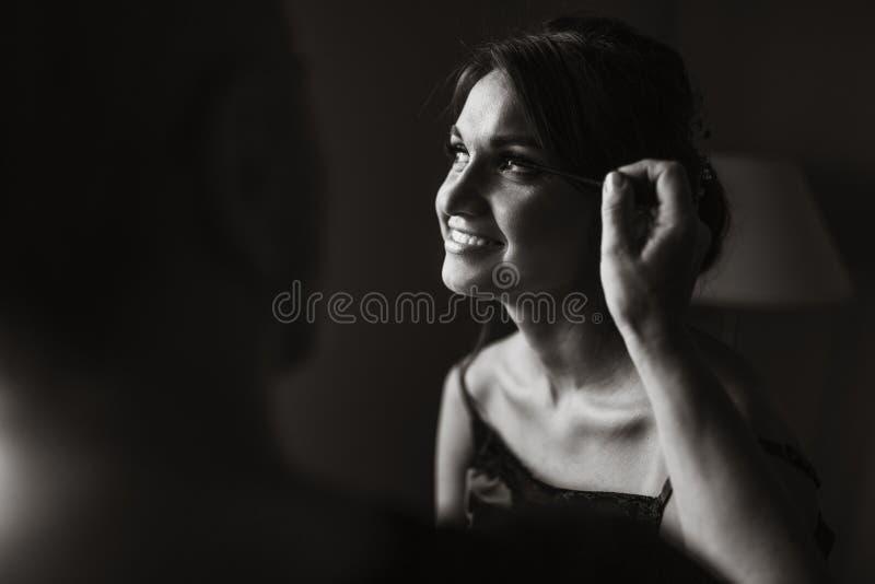De mooie bruid, make-upkunstenaar doet de huwelijksmake-up aan het meisje royalty-vrije stock foto