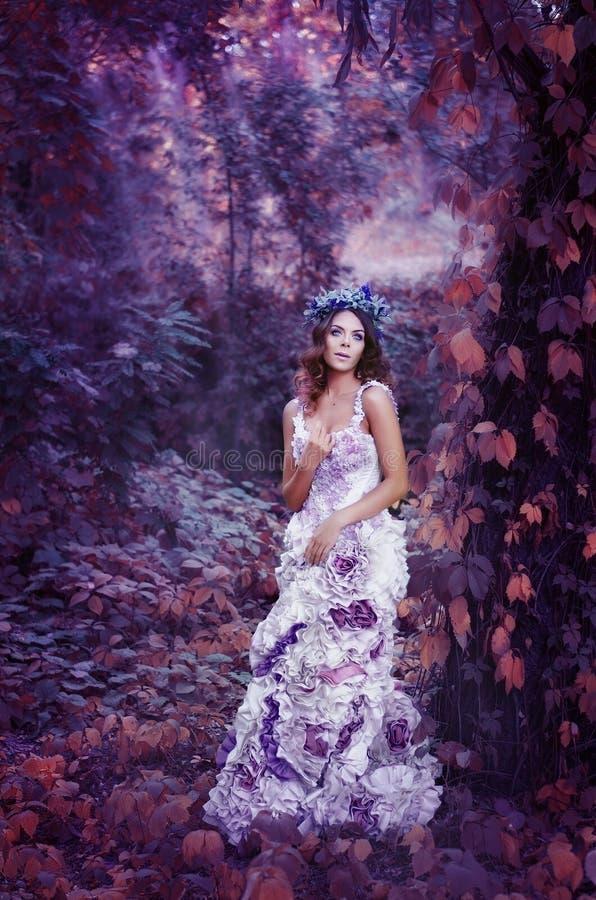 De mooie bruin-haired vrouw in een lange witte kleding, met een kroon van lavendel op haar hoofd, is in het feebos stock foto's