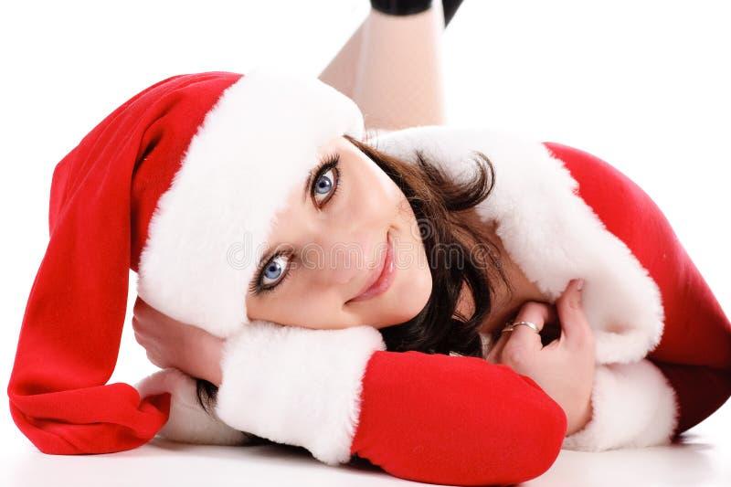 De mooie brunette in het kostuum van de Kerstman legt op vloer. stock afbeelding