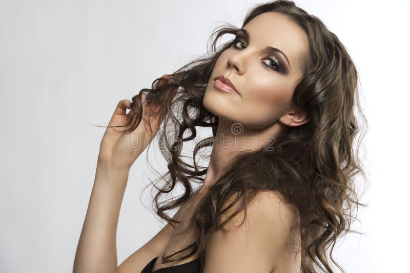 De mooie brunette met krullend haar met dient h in royalty-vrije stock foto