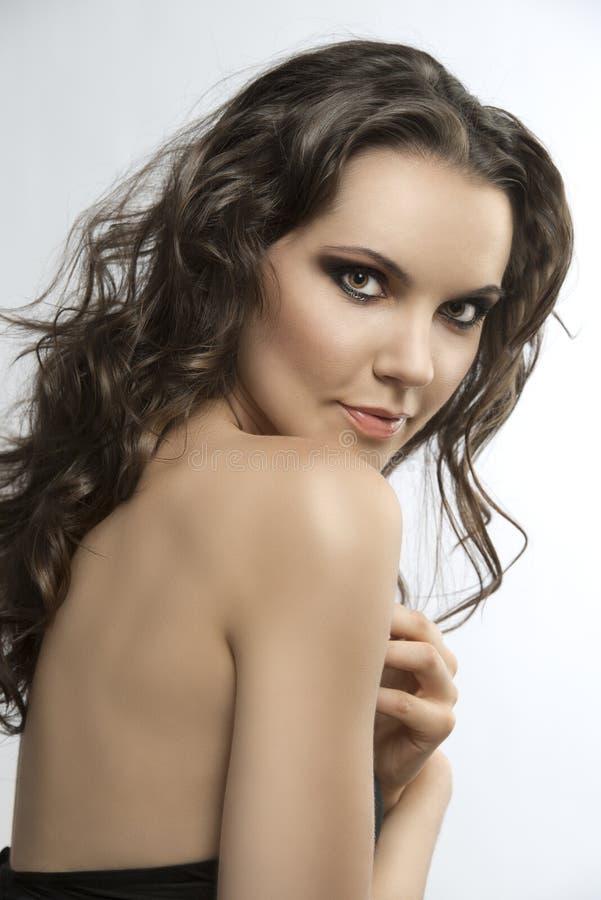 De mooie brunette met krullend haar met dient h in stock foto