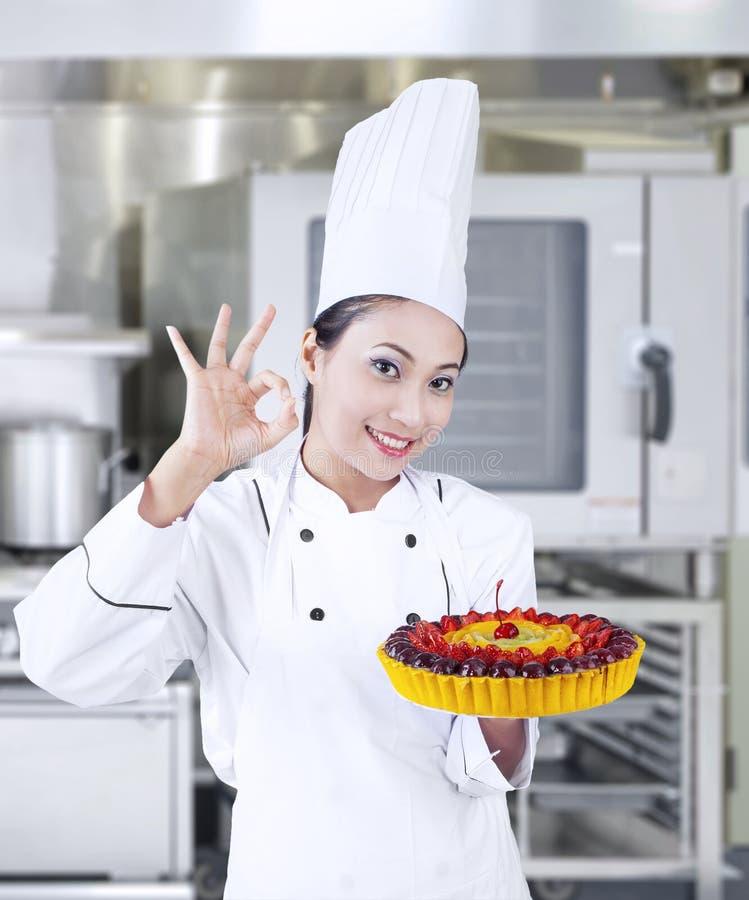 Chef-kok die heerlijke cake houden op het werk royalty-vrije stock foto's