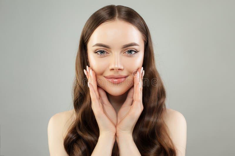 De mooie Close-up van het Gezicht van de Vrouw Gezond model met duidelijke huid die en camera glimlachen bekijken stock foto's