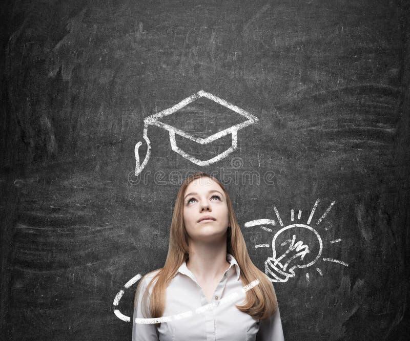 De mooie dame denkt over onderwijs Een graduatiehoed en een gloeilamp worden getrokken op het bord boven de dame royalty-vrije stock fotografie