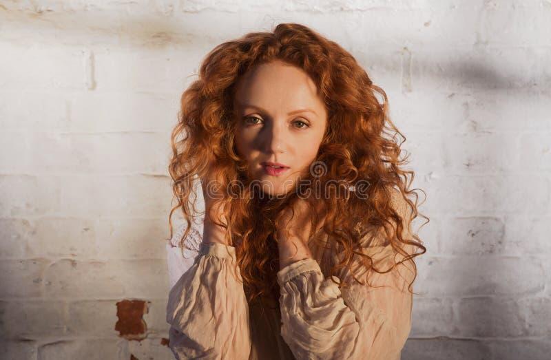 De mooie dame met lang golvend rood haar, leidt tot een kom gevormd in handen stock afbeeldingen