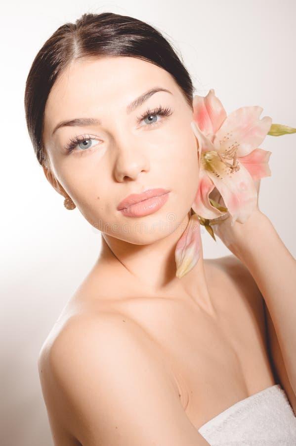 De mooie dame met lilly bloeit Perfecte huid royalty-vrije stock afbeeldingen