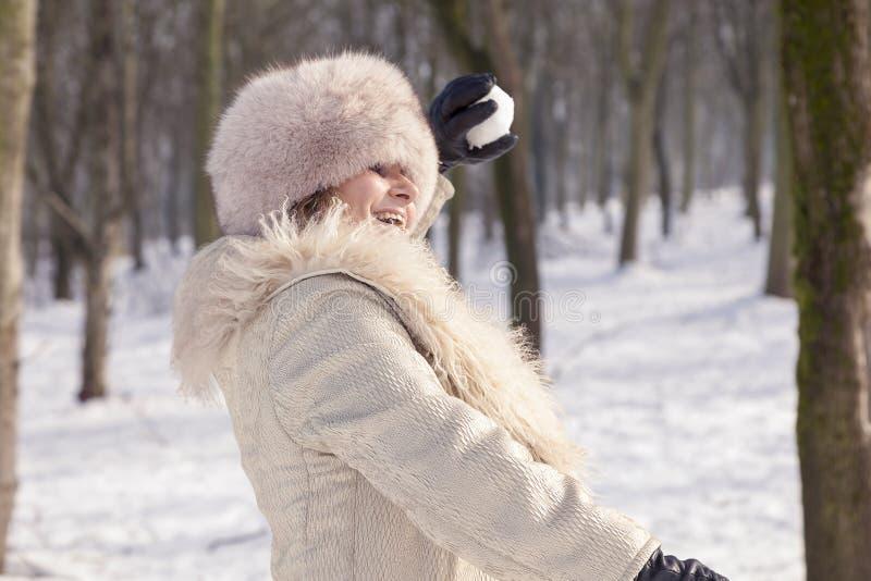 De mooie dame trekt sneeuwballen in het hout stock fotografie