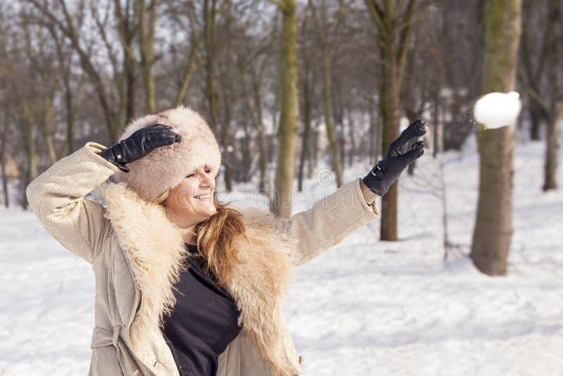De mooie dame trekt sneeuwballen in het hout royalty-vrije stock afbeelding