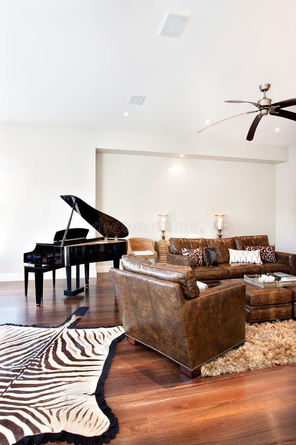 De mooie de banklijst en piano met gestreept gedrukt tapijt trekken binnen stock foto