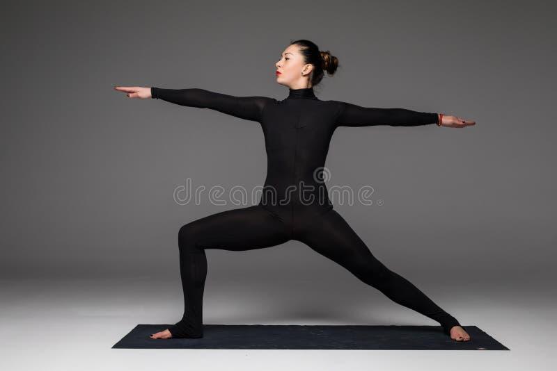 De mooie de praktijkyoga van de yogavrouw stelt op grijze achtergrond royalty-vrije stock fotografie