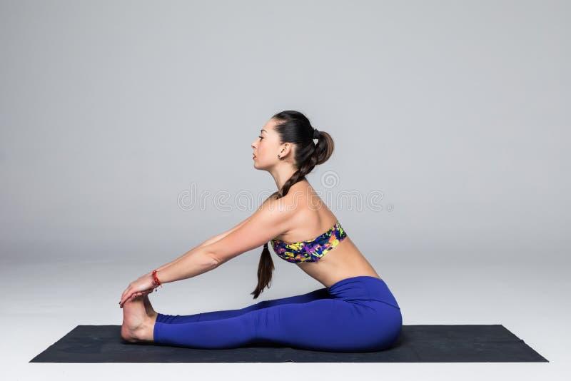 De mooie de praktijkyoga van de yogavrouw stelt op grijze achtergrond royalty-vrije stock afbeelding