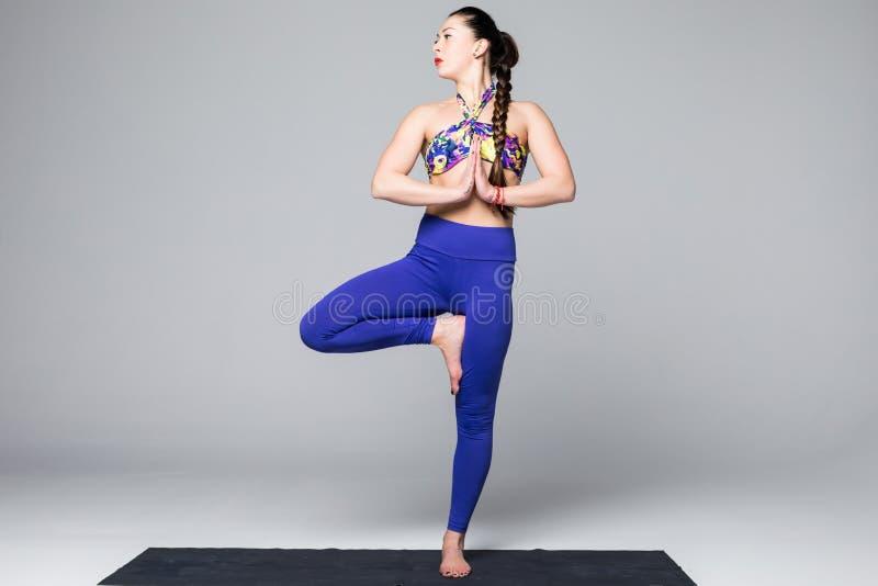 De mooie de praktijkyoga van de yogavrouw stelt op grijze achtergrond stock afbeelding