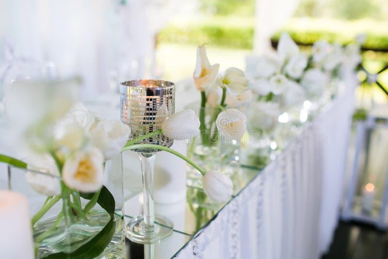 De mooie decoratie van de restaurant binnenlandse lijst voor huwelijk Bloem Witte calla lelies en tulpen in vazen Kaarsen stock foto