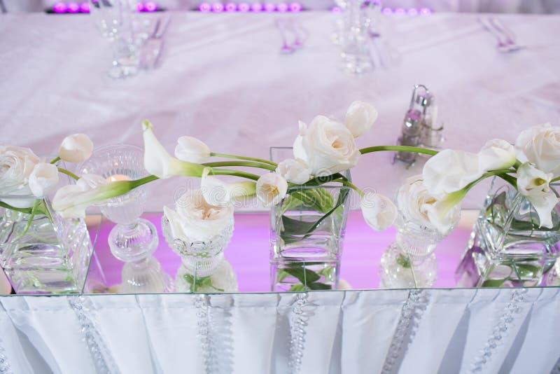 De mooie decoratie van de restaurant binnenlandse lijst voor huwelijk Bloem Witte calla lelies en tulpen in vazen Kaarsen stock afbeeldingen