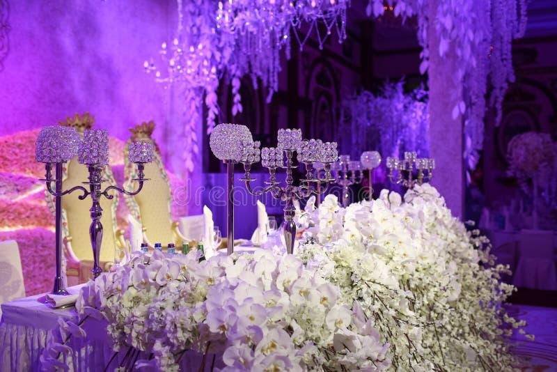 De mooie decoratie van de restaurant binnenlandse lijst voor huwelijk Bloem Witte orchideeën en sakura in vazen Kaarsen stock afbeeldingen