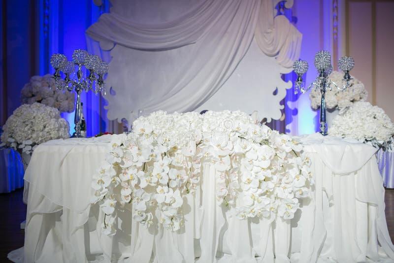 De mooie decoratie van de restaurant binnenlandse lijst voor huwelijk Bloem Witte orchideeën in vazen luxekaarsenhouders royalty-vrije stock foto's