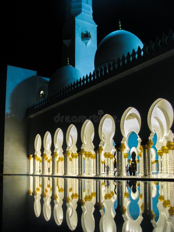 De de mooie details en architectuur van Abu Dhabi Sheik Zayed Mosque met bezinningen over water bij nacht royalty-vrije stock afbeelding