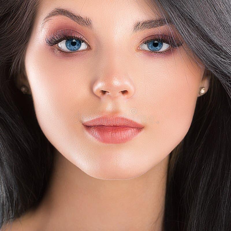De mooie dichte omhooggaande studio van het donkerbruine vrouwengezicht op wit royalty-vrije stock afbeelding