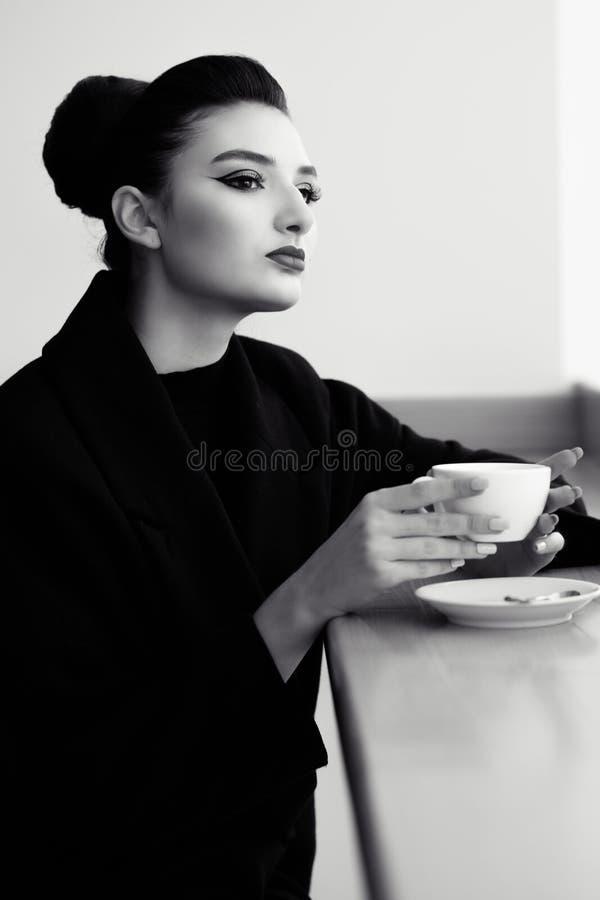 De mooie die dame met perfect maakt omhoog en haar terug in een hoge broodjeszitting bij de de bar en het drinken koffie wordt af stock afbeelding