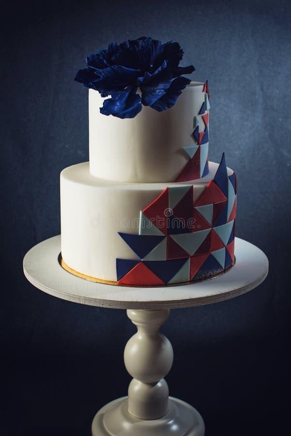 De mooie die huwelijkscake met grote blauw wordt verfraaid nam op bovenkant toe royalty-vrije stock afbeelding