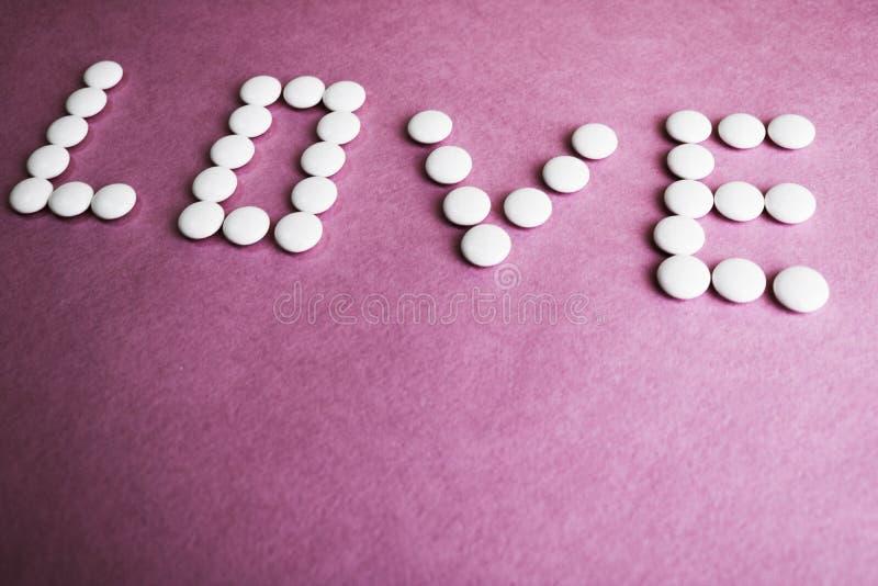 De mooie die inschrijvingsliefde van witte ronde vlotte medische pillen wordt gemaakt, de vitaminen, de antibiotica en de copie p royalty-vrije stock foto