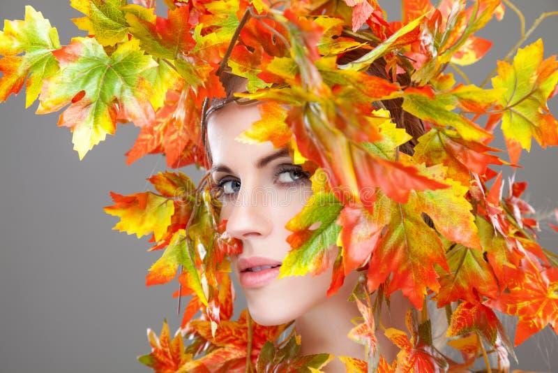 De mooie die vrouw in de herfst wordt verpakt doorbladert stock afbeeldingen
