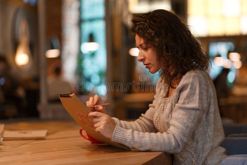 De mooie donkerbruine bedrijfsvrouw maakt nota's in haar blocnote in comfortabel restaurant gekleed in gebreid grijs sweather stock afbeeldingen