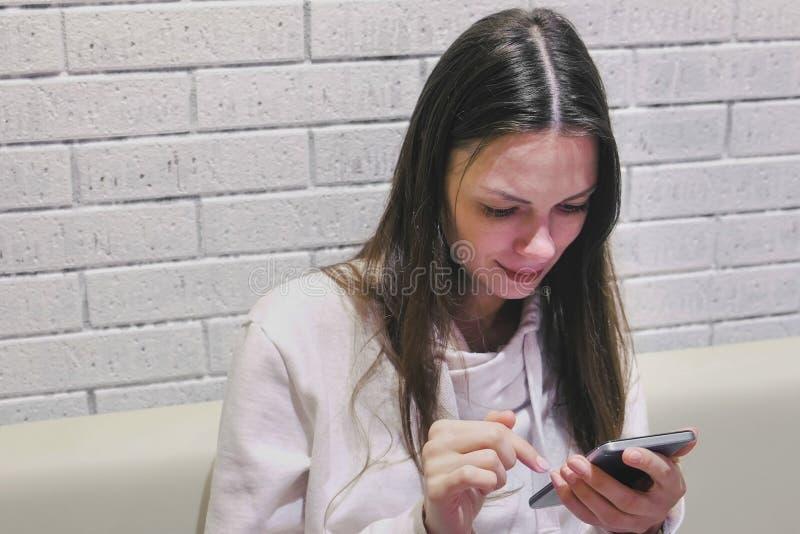 De mooie donkerbruine glimlachende vrouw typt en schuurt een bericht op mobiel telefoonzitting en wachten somebody in koffie royalty-vrije stock fotografie
