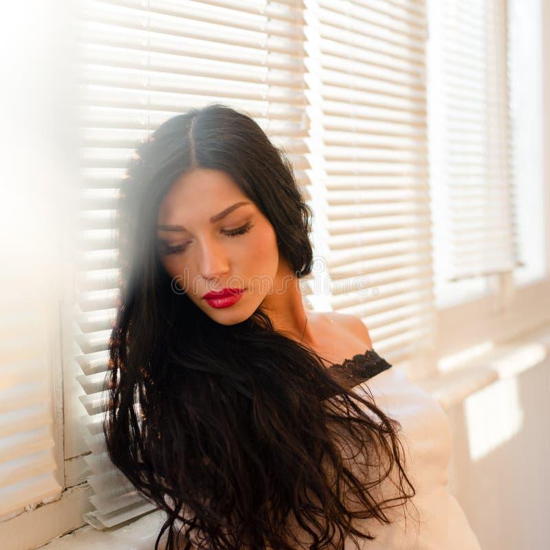 De mooie donkerbruine jonge dame die met rode lippen neer op zon aangestoken vensterzonneblinden kijken kopieert ruimteachtergron royalty-vrije stock afbeelding