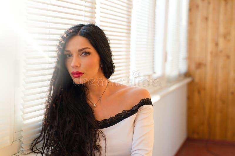 De mooie donkerbruine jonge vrouw die met blauwe ogen en rode lippen in witte kleding camera met zonlicht bekijken flakkert op ac stock foto