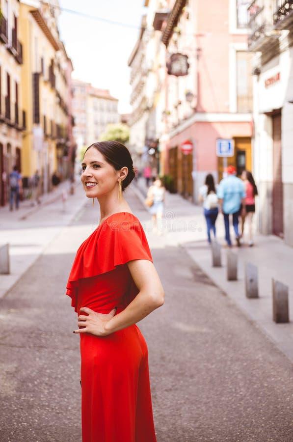 De mooie donkerbruine jonge vrouw met haarknotje die en rode ruches glimlachen dragen kleedt het lopen op de straat De foto van d stock afbeeldingen