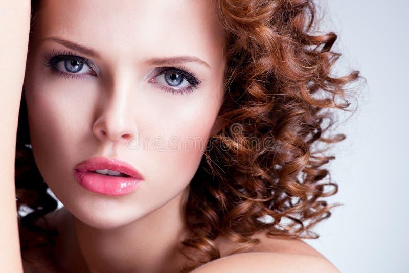 De mooie donkerbruine jonge vrouw met helder maakt omhoog stock afbeeldingen