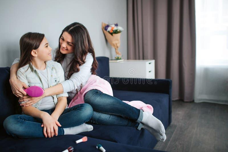 De mooie donkerbruine Kaukasische moeder en de dochter zitten samen in ruimte Het meisje en de glimlach van de mammaomhelzing aan stock afbeelding