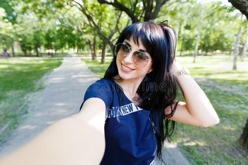 De mooie donkerbruine vrouw maakt selfie foto's kijkend aan camera royalty-vrije stock afbeeldingen