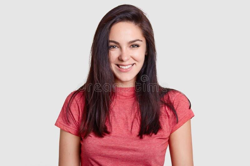 De mooie donkerbruine vrouw met prettige glimlach, donker haar, gekleed in toevallige roze t-shirt, heeft witte perfecte tanden,  royalty-vrije stock afbeeldingen