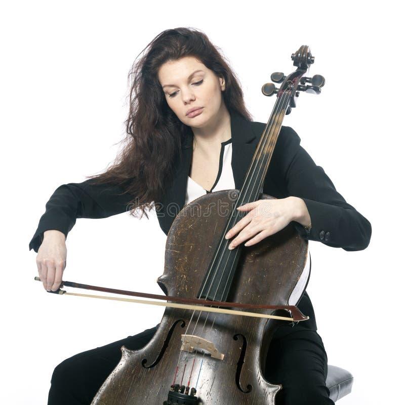 De mooie donkerbruine vrouw speelt de cello in studio tegen wit royalty-vrije stock afbeelding