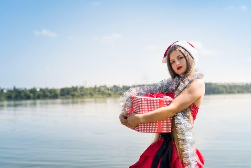 De mooie doos van de de holdingsgift van meisjessanta op kust royalty-vrije stock afbeelding