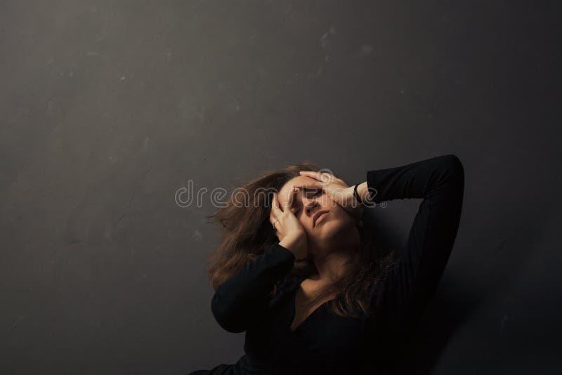 De mooie droevige jonge handen van de vrouwenholding op haar gezicht op een donkere achtergrond stock foto's