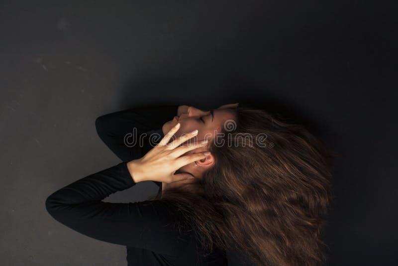 De mooie droevige jonge handen van de vrouwenholding op haar gezicht op een donkere achtergrond royalty-vrije stock afbeeldingen
