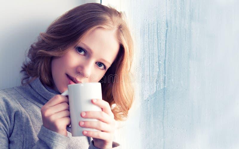 De mooie dromerige jonge vrouw met een kop van hete koffie bij wint royalty-vrije stock afbeeldingen