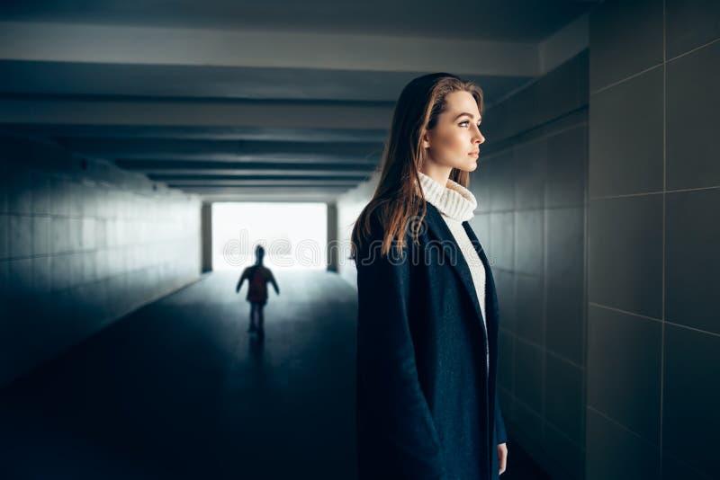 De mooie eenzame vrouw in metrotunnel met maakt silhouet bang stock foto