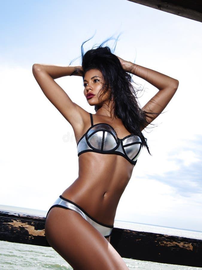 De mooie, elegante en aantrekkelijke vrouw met slank gelooid lichaam in bikini stelt dichtbij het spoor op de strandboulevard stock fotografie