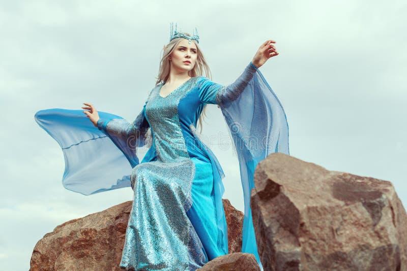De mooie elfvrouw zit bovenop een berg royalty-vrije stock afbeeldingen